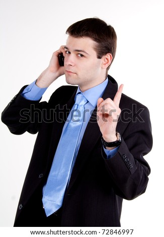 young business man talking on mobile phone and gesturing silence
