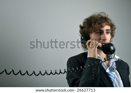 Young business man talking on old phone - stock photo