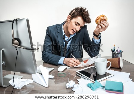 Young business man talking on the phone and writing down at his working place - stock photo
