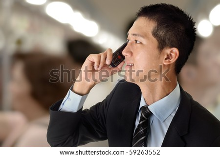 Young business man use cellphone in train. - stock photo