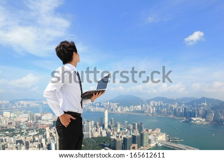 Young business man using laptop and look to cityscape, asian, hong kong - stock photo