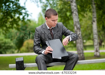 Young business man waiting for meeting, working with papers at green park. Student.