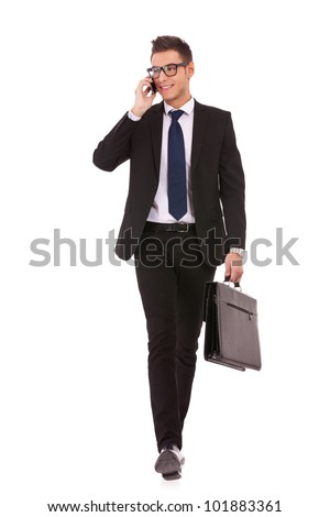 young business man walking and talking on phone while looking to a side on white background - stock photo