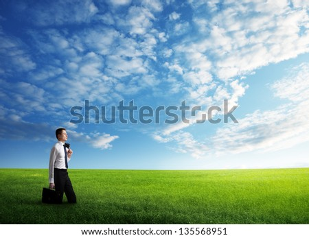 young business man walking at the field of grass - stock photo