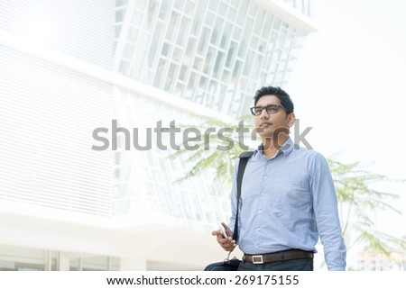 Young business man walking by a modern office building. - stock photo