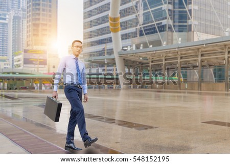 Young business man walking with his black carrying a briefcase city background, Start and Forward Concept.