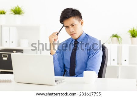 Young business man watching laptop and thinking - stock photo