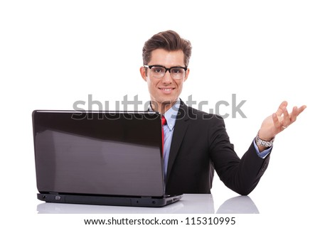young business man welcoming you at his desk with laptop isolated on white - stock photo