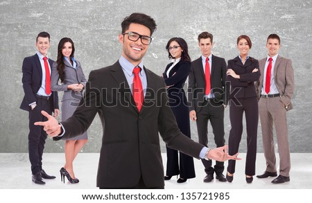 young business man welcoming you to his successful team on gray background