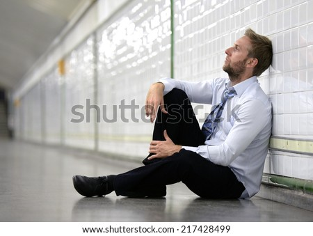 Young business man who lost job abandoned lost in depression sitting on ground street subway suffering emotional pain, thinking and leaning on wall alone - stock photo