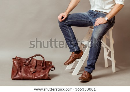 Young business man with a brown leather bag, a white shirt and blue jeans on a gray background - stock photo