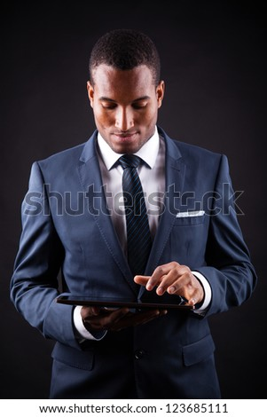 Young business man with a digital tablet on black background - stock photo