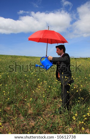 Young business man with a red umbrella and a blue watering can in a field - stock photo