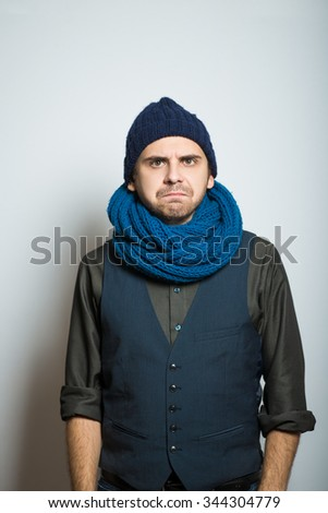 young business man with a sour face, winter style clothes, studio shot isolated on the gray background - stock photo