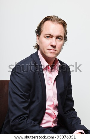Young business man with blond hair in blue suit and pink shirt serious looking isolated on white background - stock photo