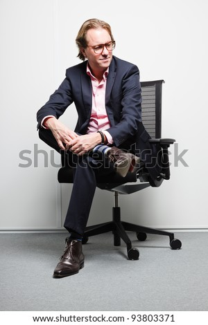 Young business man with blond hair in blue suit and pink shirt sitting on chair in office. Wearing glasses.