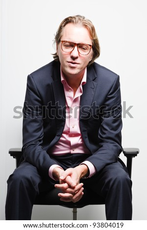 Young business man with blond hair in blue suit and pink shirt sitting on chair in office. Wearing glasses. - stock photo