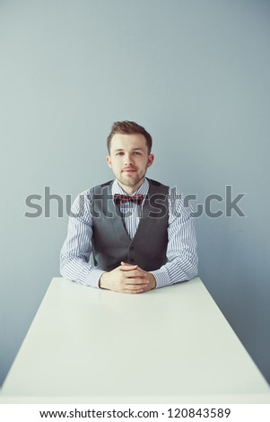 Young business man with bowtie and jacket sitting at the table - stock photo
