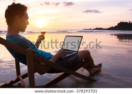 young business man with cocktail working on laptop on the beach at sunset, freelance job online, focus on the screen - stock photo