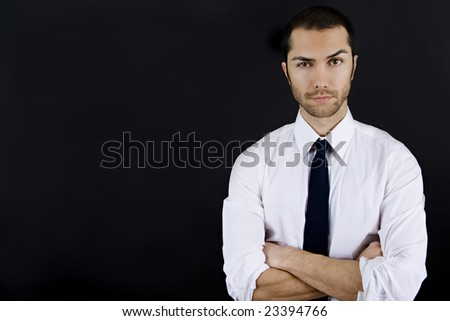 Young business man with his arms crossed and raised eyebrow - stock photo