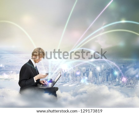 Young Business Man with Laptop and Phone on Top of the City (Cloud Computing Concept) - stock photo