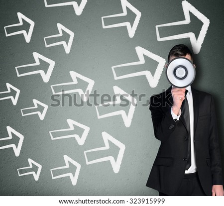 Young business man with loudspeaker and arrows pointing right - stock photo