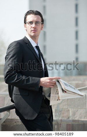 Young business man with newspaper.