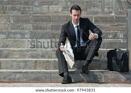 Young business man with newspaper sitting on the stairs. - stock photo