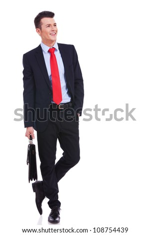 young business man with suitcase standing with his hand in pocket and looking to a side on white background