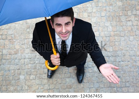 Young business man with umbrella checking if it's raining - stock photo