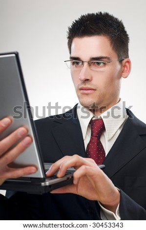 Young business man working on a laptop close up - stock photo