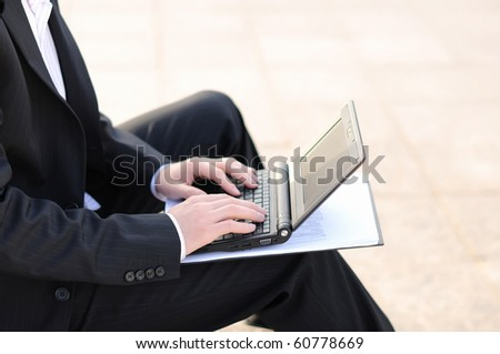 young business man working on a laptop sitting on the street