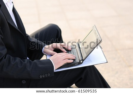young business man working on a laptop sitting on the street - stock photo