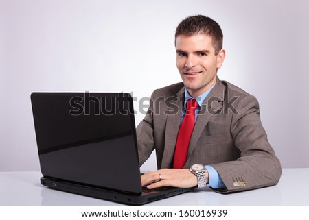 young business man working on his laptop and looking into the camera with a smile on his face. on a gray background - stock photo