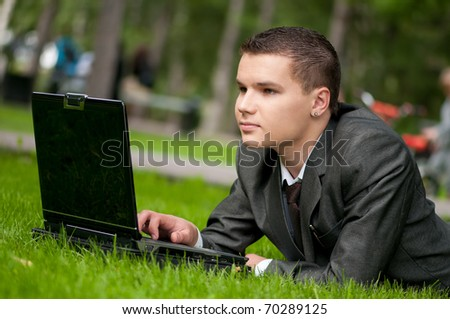 Young business man working on notebook laptop computer, at green park. Student. - stock photo