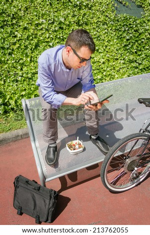 Young business man working with electronic tablet while having a lunch break, sitting on a bench outdoors - stock photo