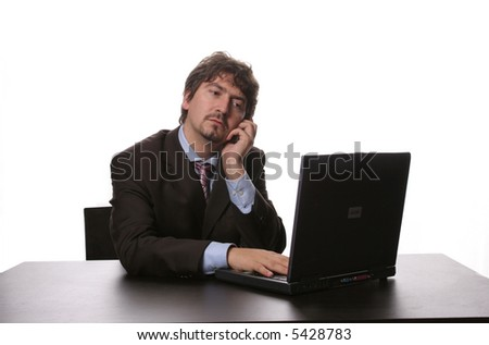 young business man working with his laptop and talking on his cellphone