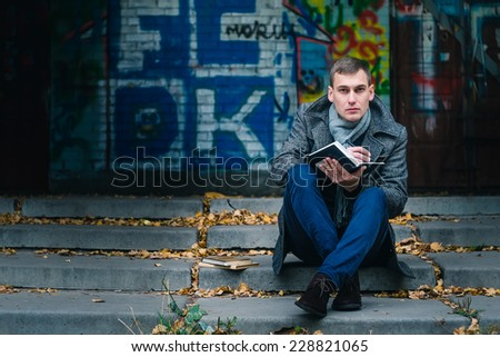 young business man writes a handle on sheets of paper sitting on the street - stock photo