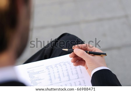 young business man writes a handle on sheets of paper sitting on the street