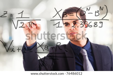 Young business man writing math formulas on the screen - stock photo
