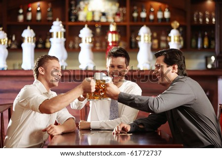 Young business men in a bar with beer - stock photo