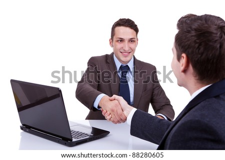 young business men reaching to an agreement at their desk, against white background - stock photo