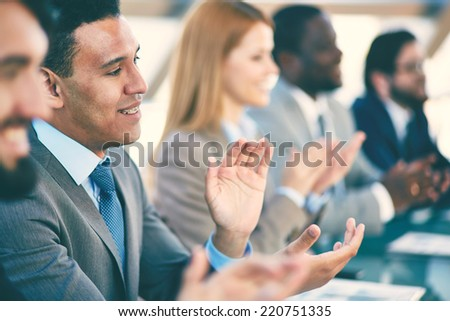 Young business partners applauding at seminar, focus on smiling man - stock photo