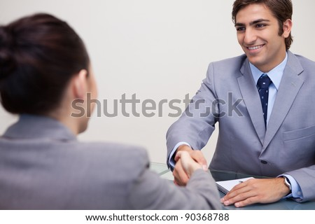 Young business partners sitting at a table shaking hands