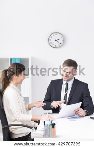 Young business partners sitting beside desk in light office