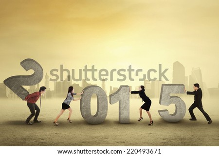 Young business people collaborate to arrange number 2015, symbolizing new business future - stock photo