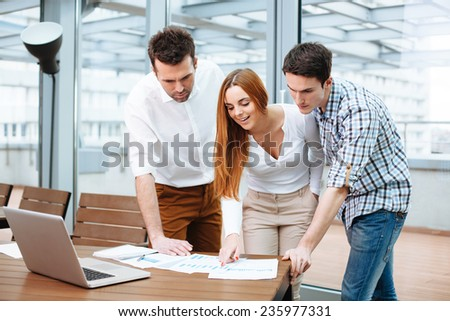 Young business people discuss financial data at office - stock photo