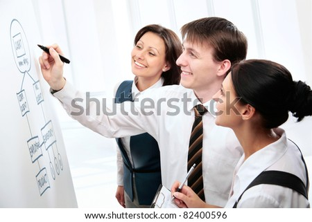 Young business people discussing something on whiteboard - stock photo