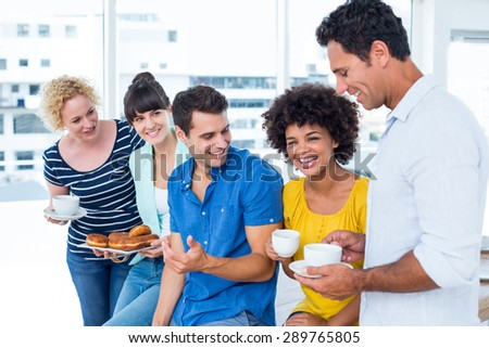 Young business people eating donuts and drinking - stock photo