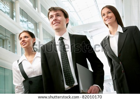 Young business people go down the hallway of a modern office - stock photo